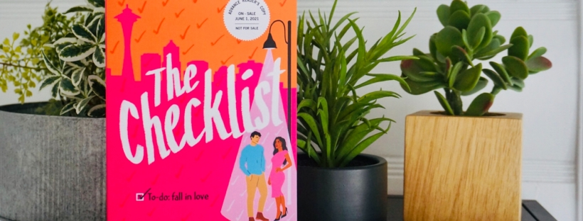 Picture of a book. The cover is pink and orange and has a man and a woman on it. The book is titled The Checklist in white lettering. In the background is the city of Seattle