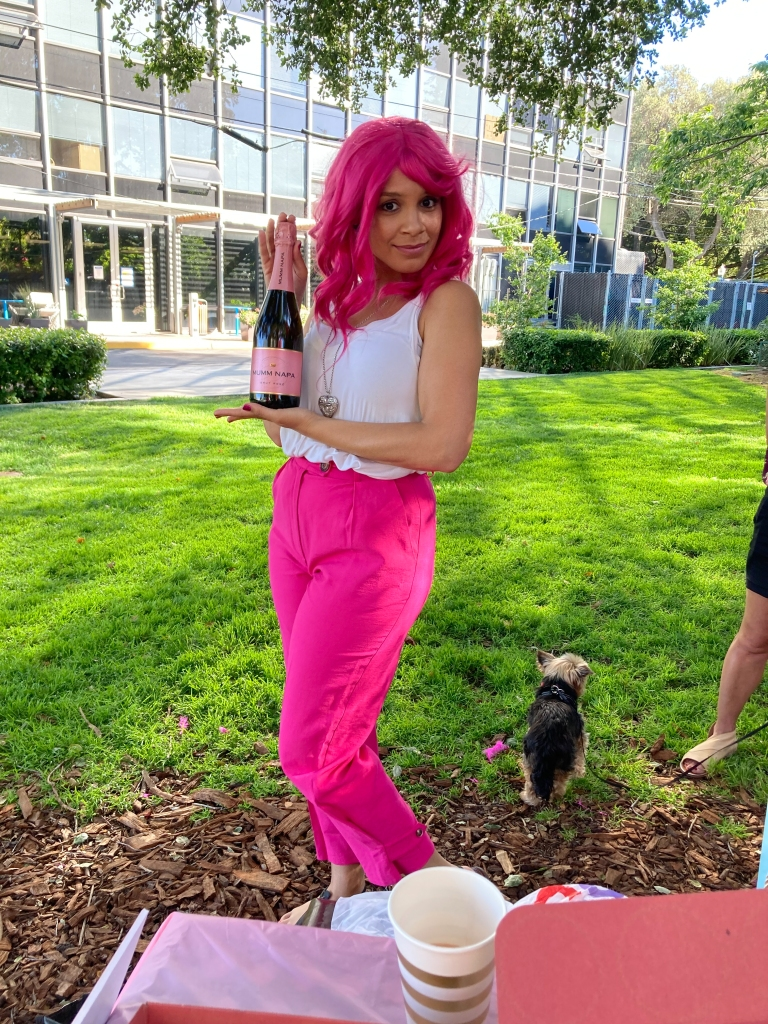 Addie Woolridge wearing a bright pink wig and bright pink pants. She is holding a bottle of Mumm Napa