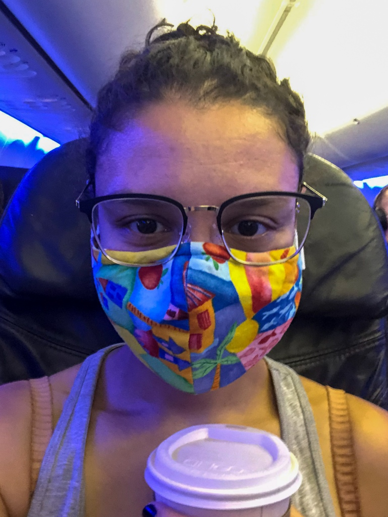 A very close up photo of Addie. Her hair is pulled back and she is wearing glasses and a brightly colored mask and  holding a cup of coffee