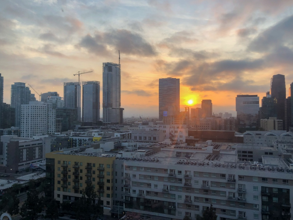 A picture of the sun setting over the Los Angeles skyline. It is taken from a rooftop.