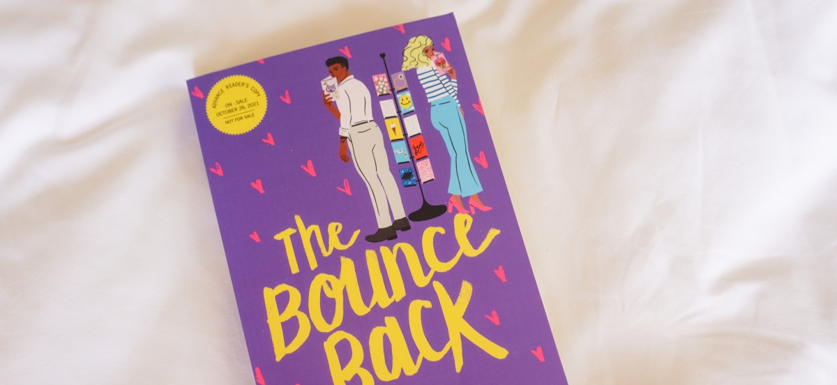 The cover of The Bounce Back. It is purple with little pink hearts. THere are two people standing in next to a rack of greeting cards, holding cards and smiling.
