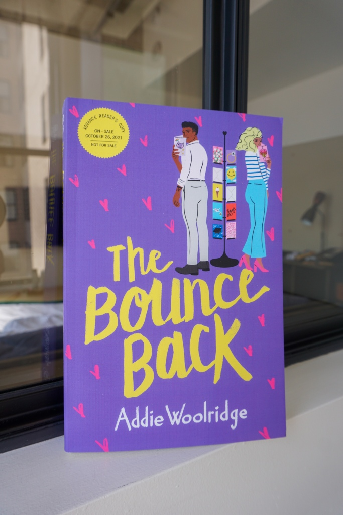 Picture of the cover of The Bounce Back, which is purple with pink hearts in the background. The title is in a yellow script font. A man and a woman are both holding greeting cards and looking over their shoulder and standing on either side of a card rack