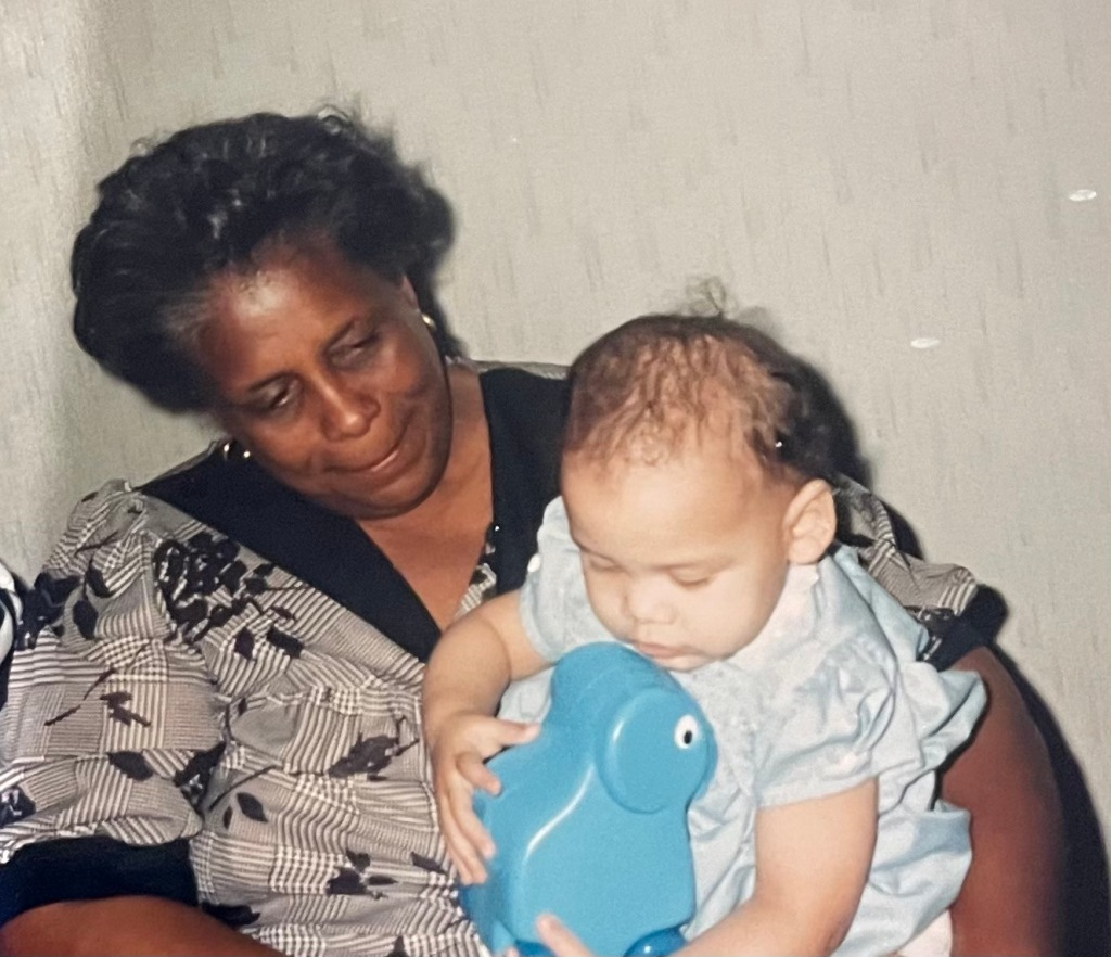 The image is of the Addie Woolridge's grandmother holding her and smiling when she was a baby. Addie is wearing a blue dress and holding a blue toy. Her grandmama has on a black and white blouse and gold earings.