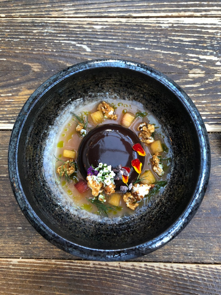 A chocolate desert in a blue bowl, covered in flowers and pieces of citrus fruit.